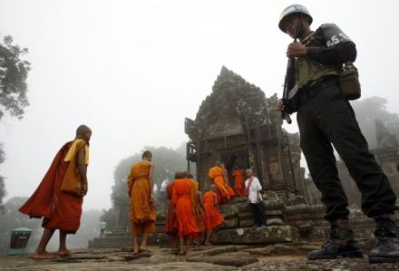 Monks walk past a soldier to attend a Buddhism ceremony praying for peace called Krong Pealy at Preah Vihear temple compound atop Dang Reak mountain
